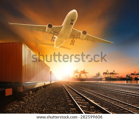industry container trainst running on railways track plane cargo flying above and ship transport in import export container yard  - stock photo