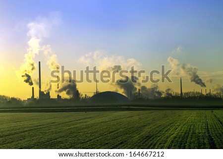 industry landscape in sunrise with smoking chimneys - stock photo