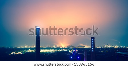 industry pollution cloud, at long exposure at twilight, of a steel factory with some irradiated chimneys in the foreground - stock photo