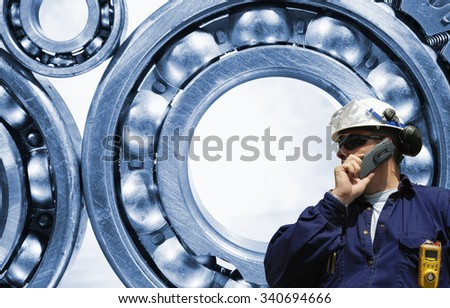 industry worker and giant ball-earings in the background - stock photo