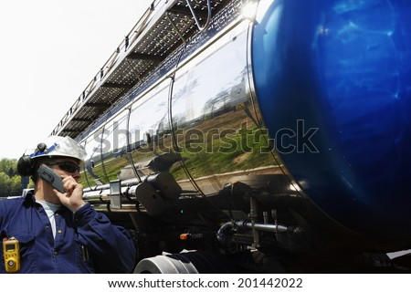 industry worker, driver talking in phone, large fuel-truck in the background - stock photo