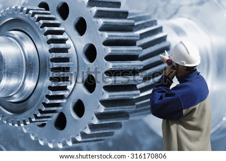 industry worker, engineer pointing at giant cogwheels and gears parts - stock photo