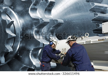 industry workers with large cogwheels and gears machinery - stock photo