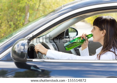 Inebriated female driver drinking alcohol directly from the bottle as she steers her car along the road posing a danger to others - stock photo