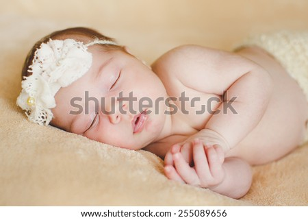 Infant baby boy sleeping peacefully. Little newborn baby boy 14 days, sleeps. infant sleeps in a dream emotions. Carefree sleep little baby with a soft toy on the bed - stock photo