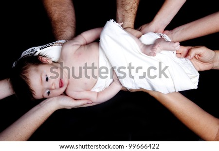 Infant baby girl held by many hands as though supported by  family or by the community perhaps for a blessing or other  religious ceremony over black backdrop. - stock photo