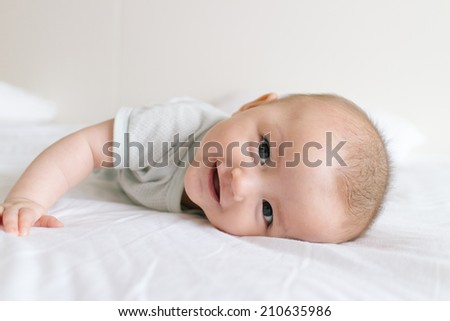 Infant baby girl lying on white bed and looking at camera - stock photo