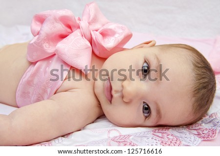 Infant baby with a pink ribbon bow tied on her chest