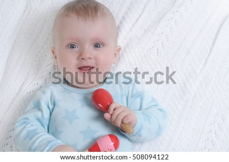 Infant boy lying in bed and holding red maracas. Happy family concept