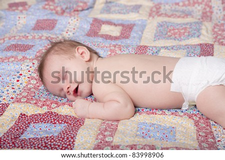 Infant boy sleeping on blanket with smile on face - stock photo