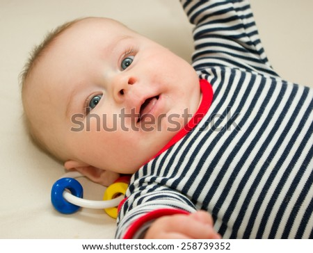 Infant boy with wide opened blue eyes laying on a blanket - stock photo