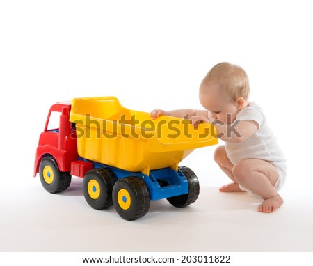 Infant child baby boy toddler happy sitting with big toy car truck red yellow and blue colors in hand on a white background