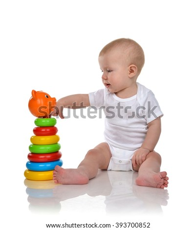 Infant child baby boy toddler playing with Pyramid in hand on a floor isolated a white background - stock photo