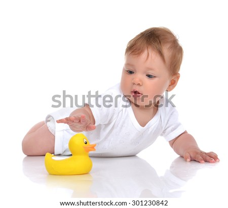 Infant child baby boy toddler playing with yellow duck toy in hand on a floor isolated a white background