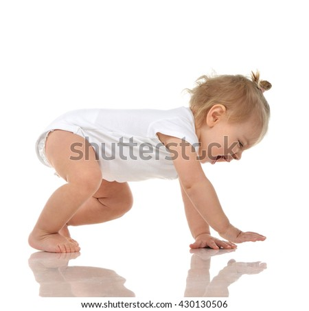 Infant child baby girl in diaper crawling happy laughing smiling looking down isolated on a white background