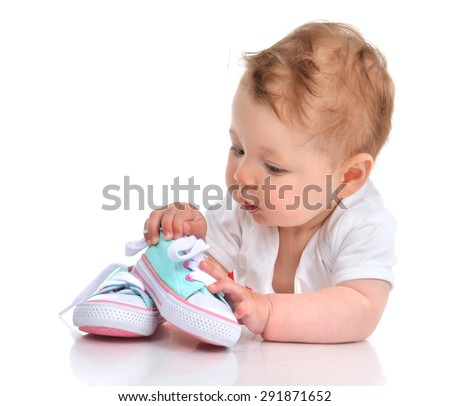 Infant child baby girl lying happy searching new shoes isolated on a white background - stock photo