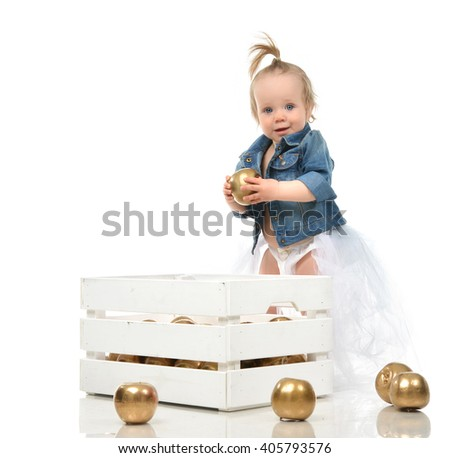 Infant child baby girl toddler standing with box and gold apples isolated on a white background - stock photo