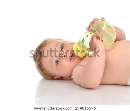 Infant child baby kid lying and drinking water from the feeding bottle on a white background - stock photo