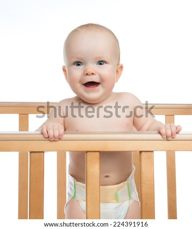 Infant child baby toddler in wooden bed looking up happy smiling on white background