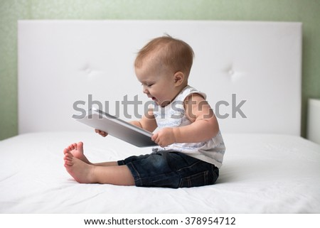 Infant child baby toddler sitting and typing digital tablet mobile computer on white background - stock photo