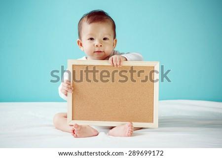 Infant child holding empty board, studio shot - stock photo