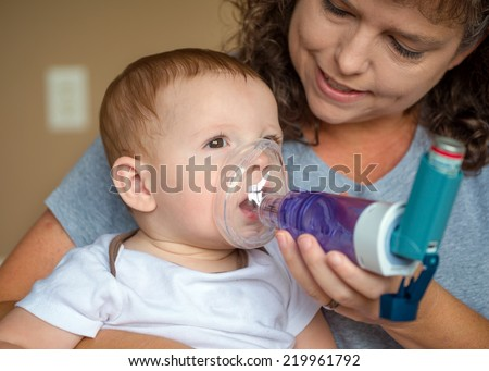Infant getting breathing treatment from mother while suffering from illness - stock photo