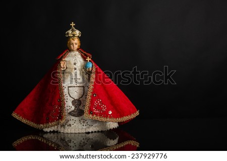 Infant Jesus of Prague in red vestments on a dark background - stock photo