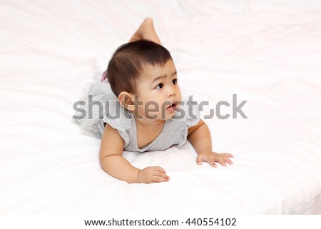 Infant playing on bed and smile happily