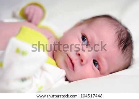 Infant Preparing for Diaper Change. Three-week old baby boy looking to the left of frame as if he is about to have his diaper changed. Shallow DOF. - stock photo