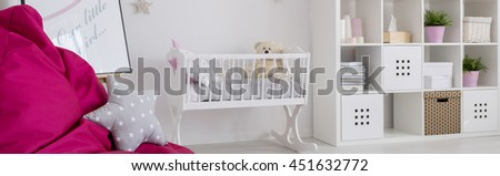 Infant room with white cradle, regale and pink sack chair - stock photo