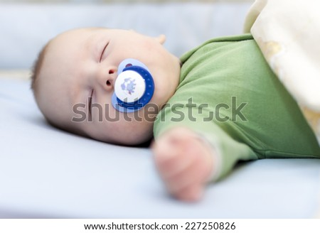 Infant sleeping with soother in his mouth - stock photo