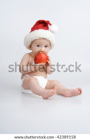 Infant with apple and Christmas bonnet on white background. - stock photo