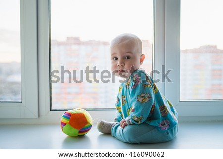 Infant with toy sitting alone near window, high-rise buildings on background - stock photo