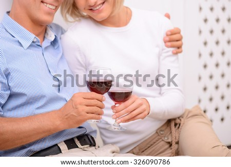 Infatuated with you. Content loving adult couple holding glasses and drinking wine while bonding to each other - stock photo