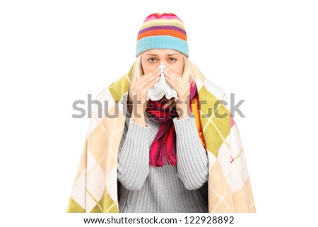 Infected woman covered with blanket blowing her nose in tissue paper because of being ill isolated on white background - stock photo
