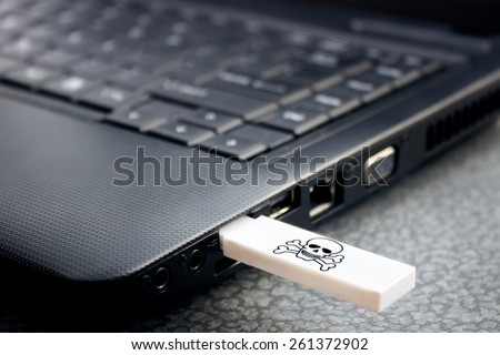 infecting a portable computer with a virus via USB - stock photo