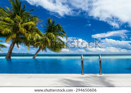 infinity pool with coco palms in front of tropical  landscape - stock photo