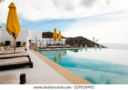 infinity pool with yellow umbrellas - stock photo