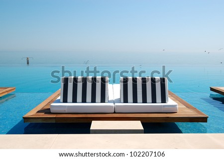 Infinity swimming pool by beach at the modern luxury hotel, Pieria, Greece - stock photo