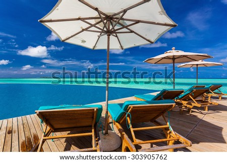 Infinity swimming pool on the beach of tropical island with white beach umbrellas and chairs - stock photo
