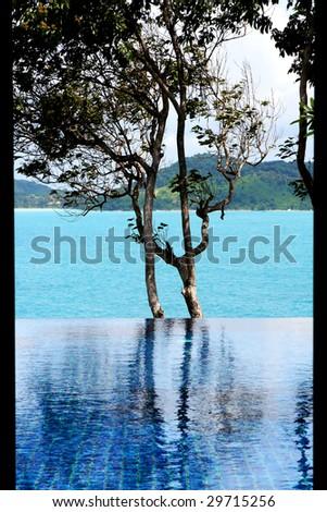 Infinity swimming pool overlooking the ocean. (Black frame is villa door). - stock photo