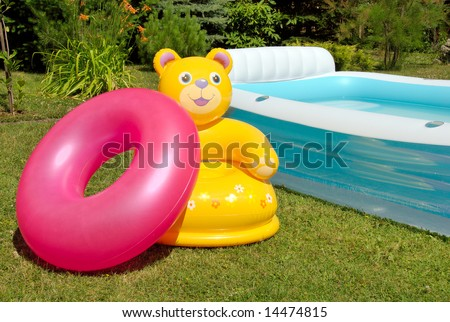 Inflatable armchair and tire near the pool - stock photo