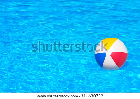 Inflatable ball floating in swimming pool - stock photo