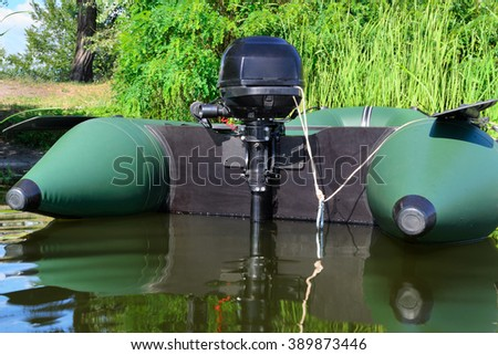 Inflatable boat with motor on the river near a shore