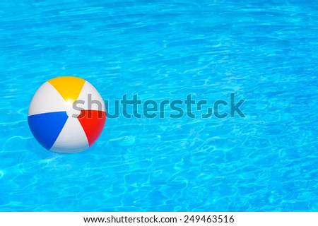 Inflatable colorful ball floating in the swimming pool - stock photo
