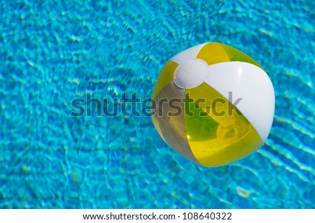 Inflatable yellow beachball floating at the water - stock photo