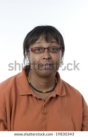 informal portrait of a black middle-aged woman slightly smiling wearing glasses looking directly at the camera - stock photo