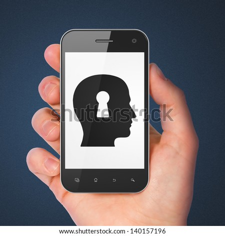 Information concept: hand holding smartphone with Head Whis Keyhole on display. Generic mobile smart phone in hand on Dark Blue background. - stock photo