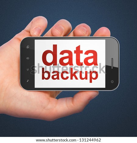 Information concept: hand holding smartphone with word Data Backup on display. Generic mobile smart phone in hand on Dark Blue background. - stock photo