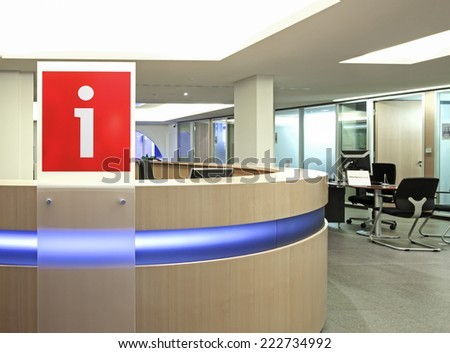 "Information point in office building with red plastic sign ""i"" written on it"